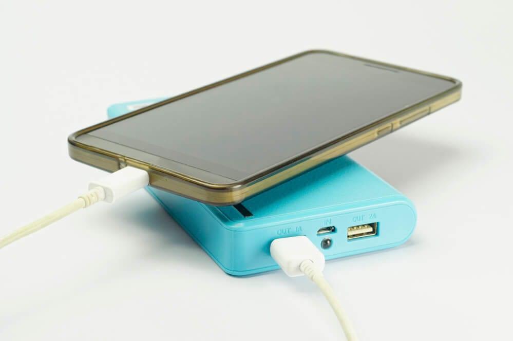 carregador portátil azul carregando telefone celular com capa